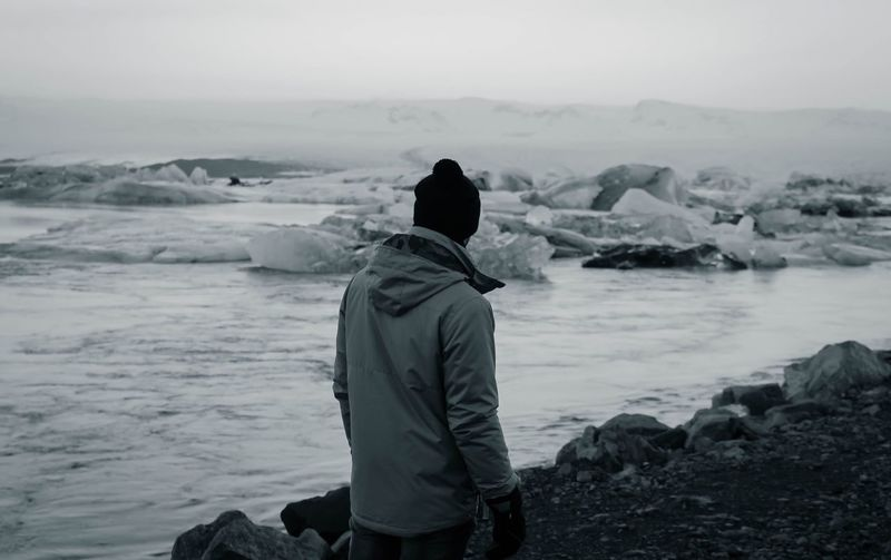 Man standing on rock against sea during winter