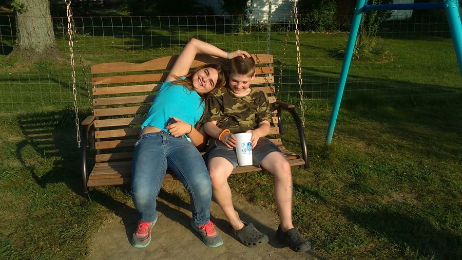 Brother and sister sitting on swing at grassy field