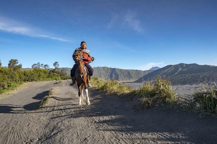 Man Horseback Riding On Sand At Desert