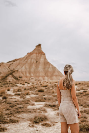 Rear view of woman standing at desert