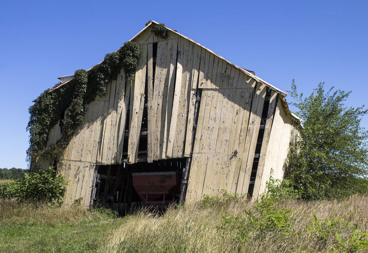 A decaying wooden barn in a rural area. Abandoned Nature Sky Architecture Built Structure Old Day No People Clear Sky Land Damaged Field Sunlight Weathered Run-down Outdoors Ruined Agriculture Weathered Old Barn Barns Rural Decay Doors Country Life Countryside Deterioration