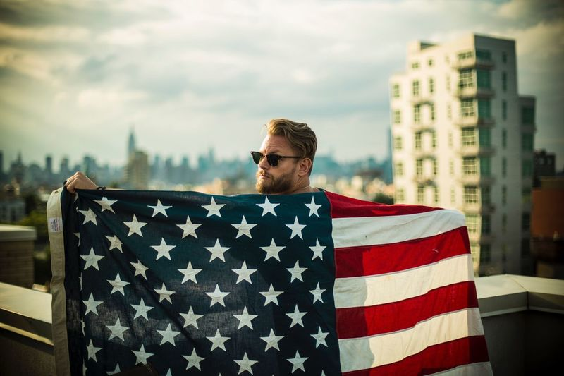 Portrait of man with american flag standing in city