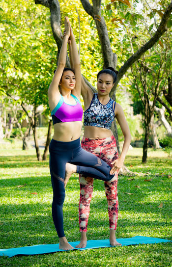 Yoga instructor assisting woman while exercising at park
