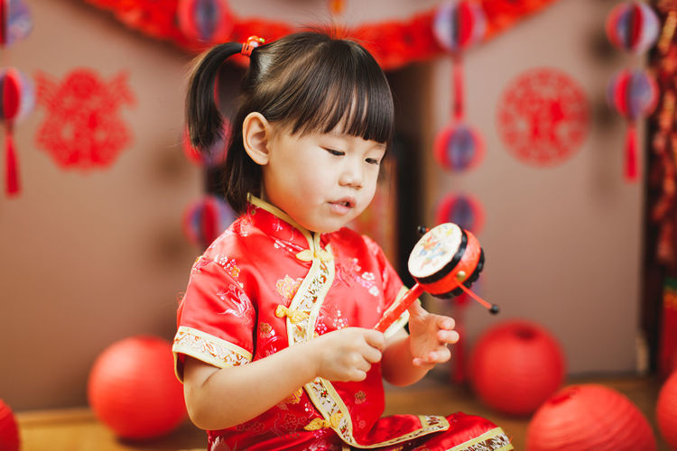 Cute baby girl holding toy at home
