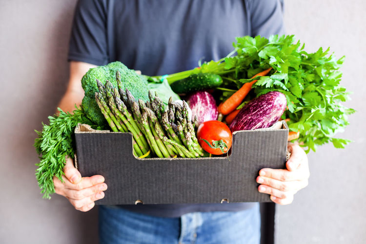 Midsection of man holding vegetables in box