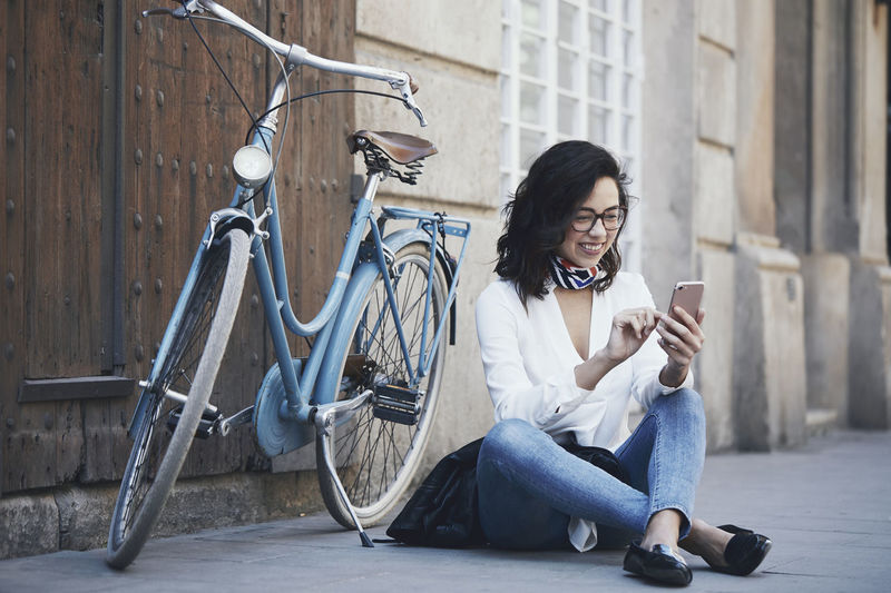Full length of woman using mobile phone while sitting by bicycle on sidewalk