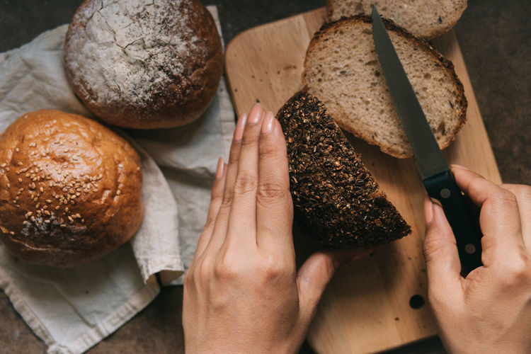 Close-up of hands cutting bread