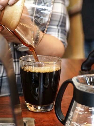 Midsection Of Person Pouring Black Coffee In Glass On Table