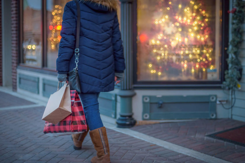 Back View Carrying Christmas City Lights Shopping Sidewalk Winter Wintertime Woman Bags Coat Decorations Display Female Jacket One Person Outdoors person Season  Walking Window