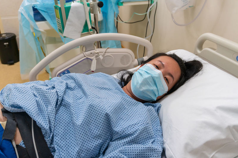 High angle view of woman lying on bed at hospital