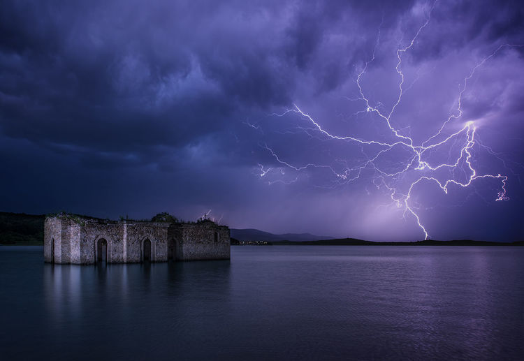 Old ruins in lake against lightning at night