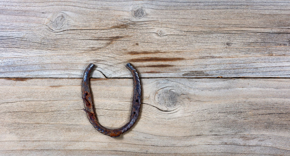 rusty horseshoe on rustic wooden boards in overhead view Copy Space Holiday Horseshoe Luck Rustic St Patrick's Day Wood Good Irish Metal St Patrick