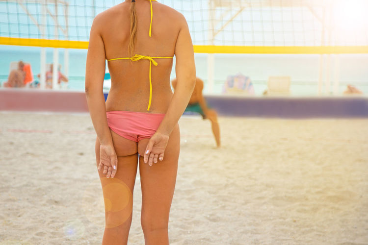 Midsection of woman standing at beach