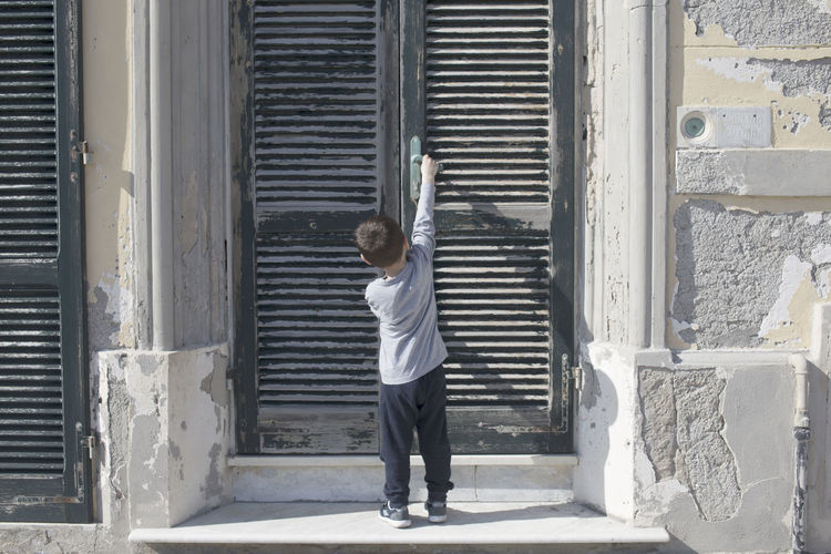 Rear View Of Boy Standing Against Closed Door