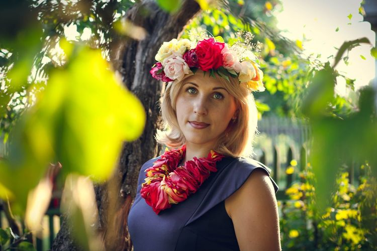 Portrait Of Young Woman Wearing Floral Necklace And Wreath In Yard