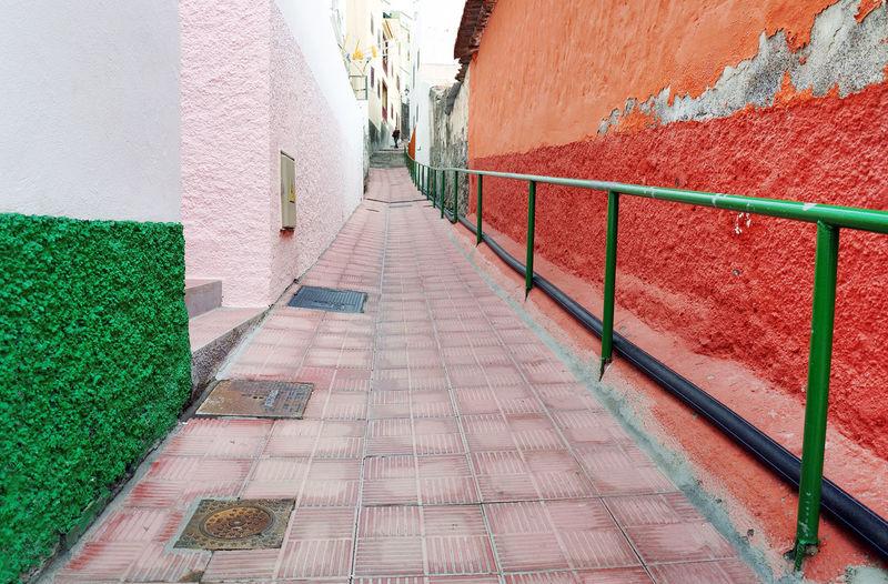Empty walkway amidst buildings