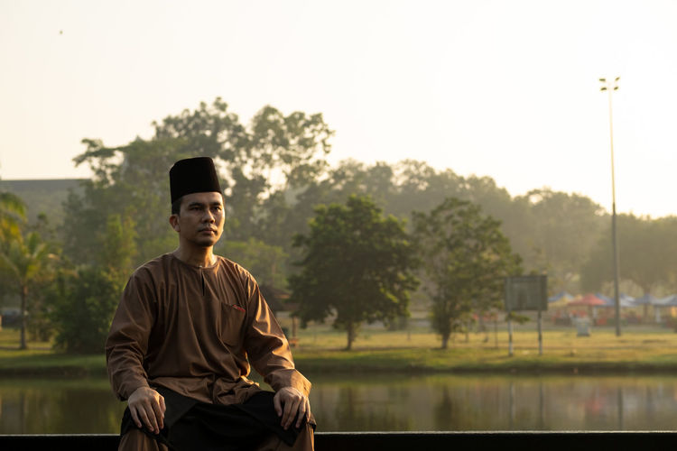 Portrait Of Man Wearing Traditional Clothing While Sitting Against Lake During Sunset