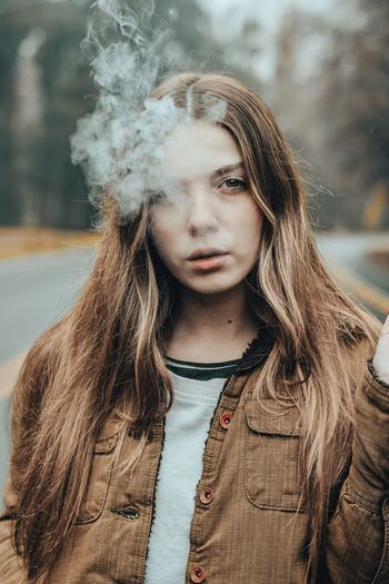 Portrait Of Beautiful Young Woman Smoking While Standing On Road