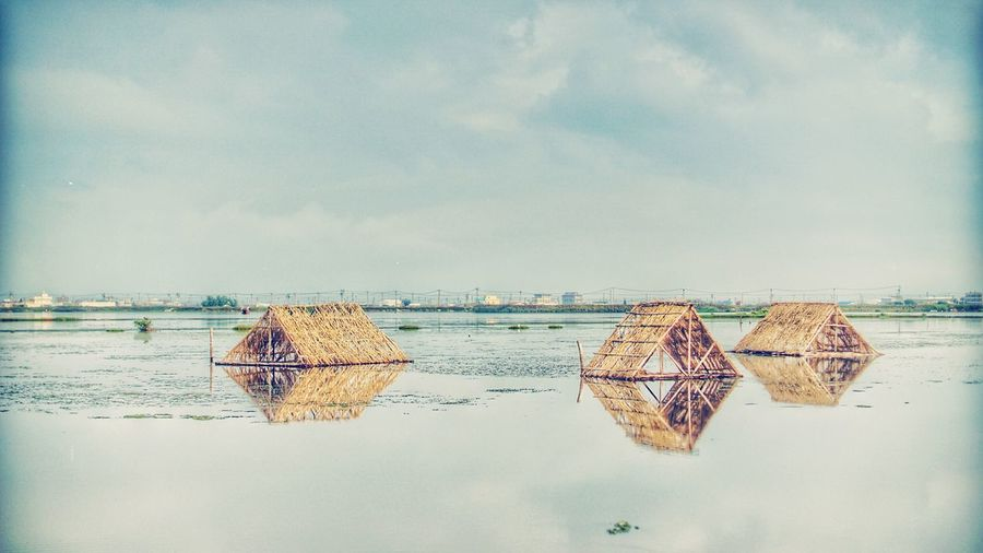 Triangle shaped huts at riverbank against sky