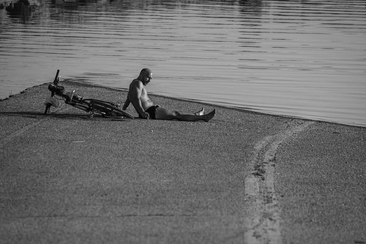 Side view of man sitting on bicycle by lake
