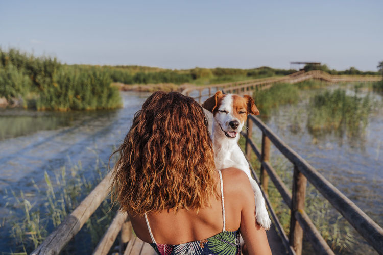 Rear view of woman with dog on footbridge against sky