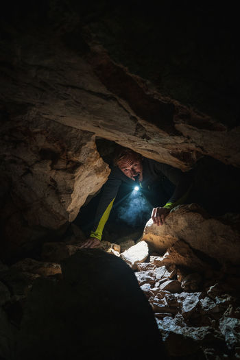 Man with flashlight exploring in cave