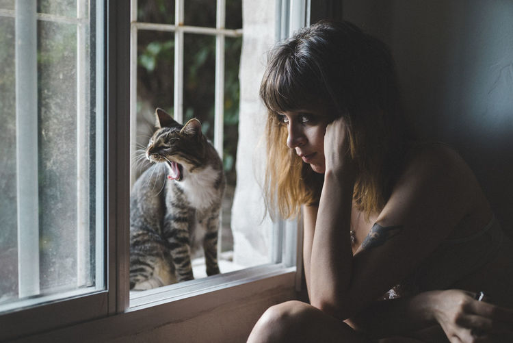 Young woman sitting by window with cat at home