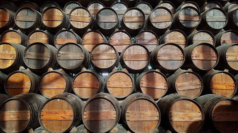 Wine barrels stack together aging wine Stack Industry Wine Porto Oporto Moscatel Liquor Whisky Madeira Portuguese Barrel Oak French Wood Round Pattern Moonshine Beverage Sweet Desert Vintage Aging Process Business Culture