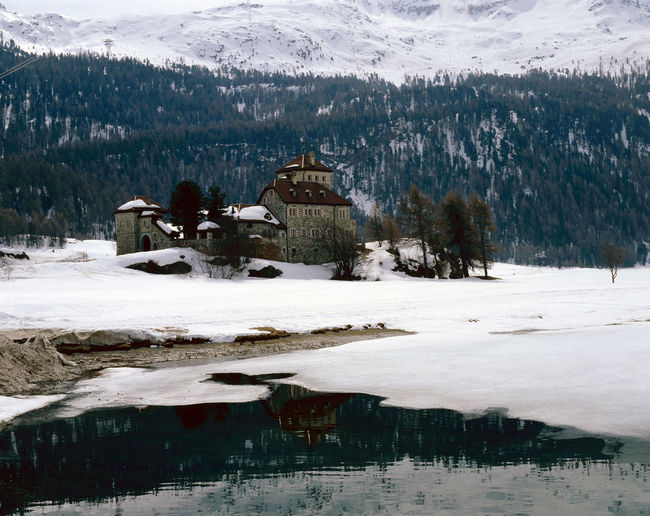 A historic castle/building in the snow covered landscape, lake and mountains in the alps Switzerland Castle Christmas Holiday Travel Architecture Beauty In Nature Building Exterior Built Structure Cold Cold Temperature Day Historic Lake Mountain Nature No People Outdoors Reflection Scenics Snow Tranquility Travel Destinations Tree Water Winter