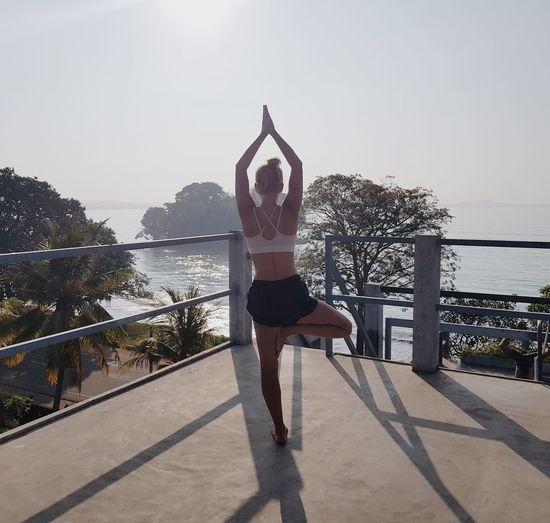 Woman doing yoga tree pose Doing Yoga Yoga Tree Pose Exercising Full Length Horizon Over Water Healthy Lifestyle Lifestyles Yoga Wellbeing Flexibility