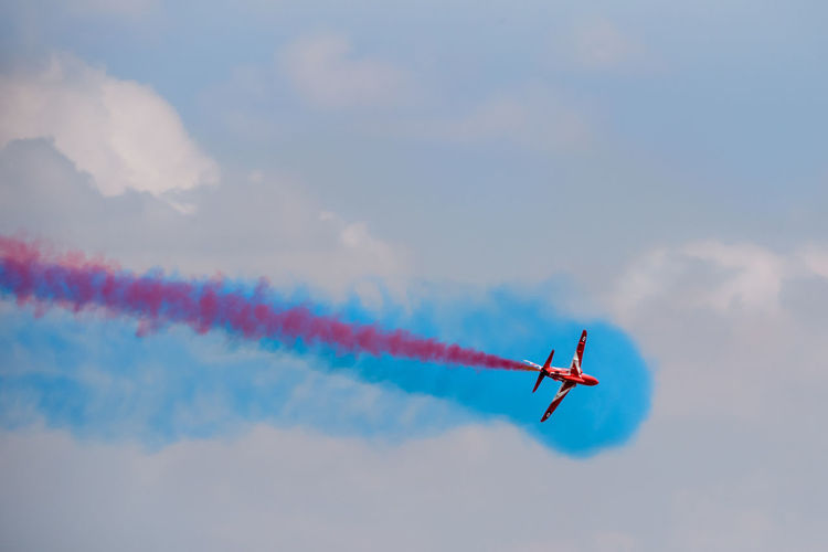 A single Red Arrow BAE systems Hawk T1 of the Royal Air Force during an air display at RIAT Fairford 2018, UK. Aerobatics Air Vehicle Airplane Airshow Blue Cloud - Sky Cooperation Fighter Plane Flying Formation Flying Low Angle View Military Airplane Mode Of Transportation Motion Multi Colored No People on the move Outdoors Plane Red Arrows Sky Smoke - Physical Structure Teamwork Transportation Vapor Trail