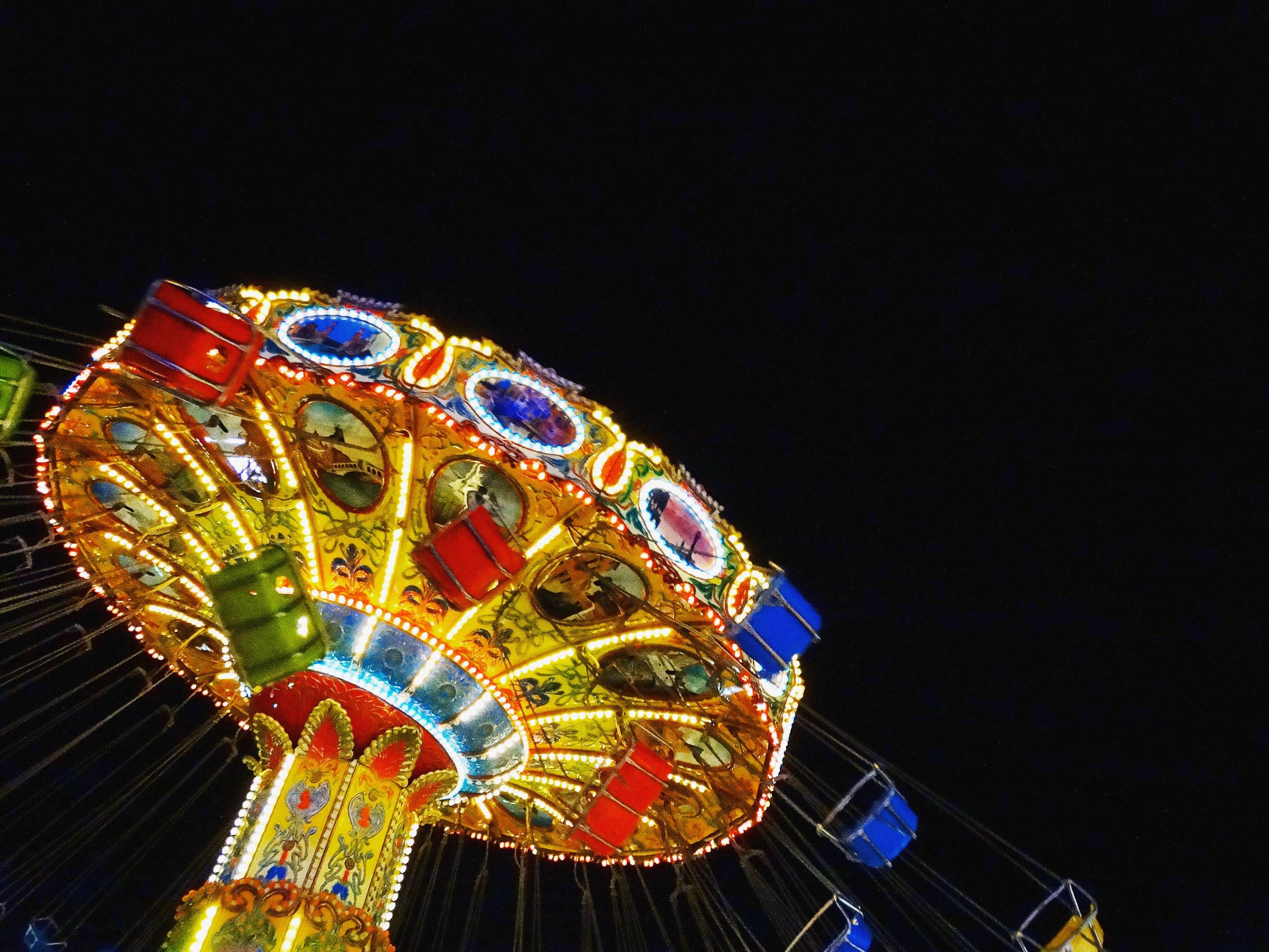 amusement park, night, illuminated, arts culture and entertainment, amusement park ride, low angle view, black background, multi colored, clear sky, no people, carousel, ferris wheel, outdoors, sky, close-up