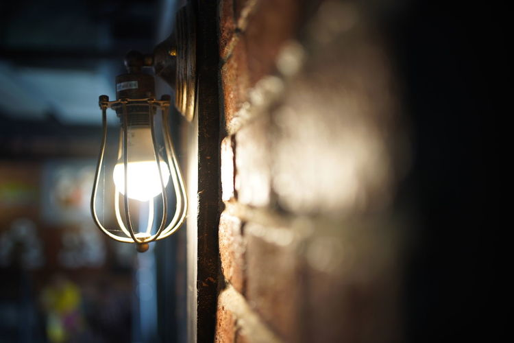 Close-up of illuminated light bulb by wall