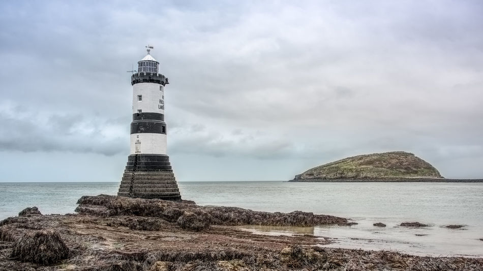 Seascape view from Anglesey in Wales of Pen Mon lighthouse and puffin island in the distance Pen Mon Puffin Island Wales Anglesey Architecture Beach Beauty In Nature Day Horizon Over Water Lighthouse No People Outdoors Sea Sky Tranquility Water