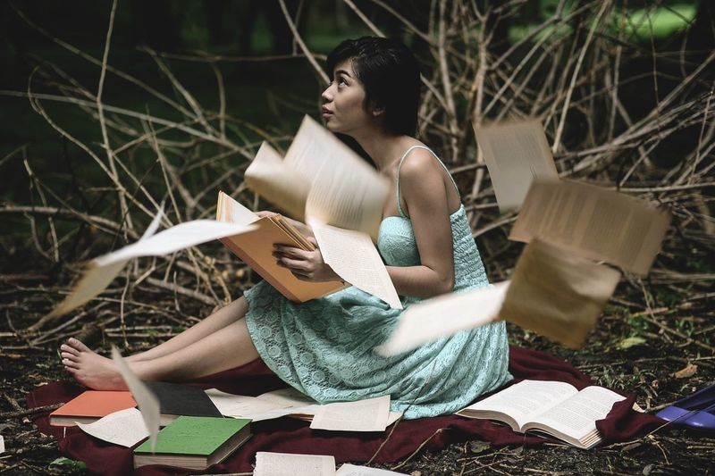 Woman sitting amid scattered books