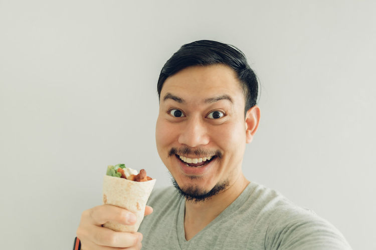 Portrait of man eating food against white background