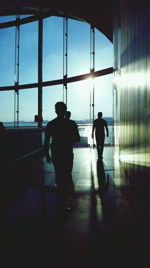 Silhouette men walking in modern building