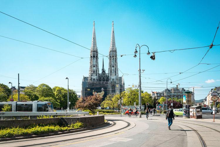 Cable Car On Street By Votive Church Against Clear Sky