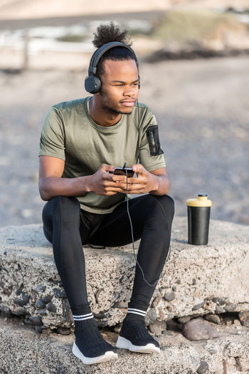 Handsome African American male listening to music and looking away while sitting near cup of hot beverage on seashore One Person Wireless Technology Technology Real People Mobile Phone Leisure Activity Communication Young Adult Portable Information Device Casual Clothing Smart Phone Young Men Lifestyles Front View Full Length Holding Using Phone Telephone Day Outdoors Man Listening To Music Smartphonephotography Headphones Looking At Camera