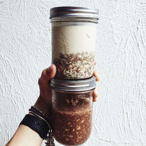 Cropped hand holding chia smoothie jars against white wall