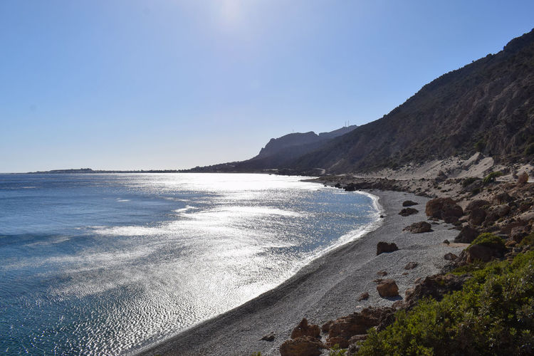 The wild and beautiful Gialiskari beach in southern Crete Beach Beachphotography Beauty In Nature Blue Clear Sky Copy Space Day Greece Idyllic Land Mountain Nature No People Non-urban Scene Outdoors Scenics - Nature Sea Sky Sun Sun Reflection Sunlight Tirquoise Tranquil Scene Tranquility Water