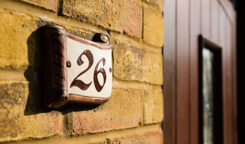 A house number next to a door. 26 Doors Architecture Building Exterior Built Structure Close-up Communication Day Door Doornumber No People Number Outdoors Text