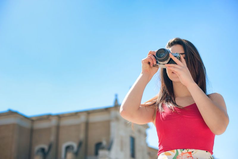 Female photographer against clear blue sky