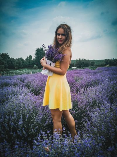 Portrait Of Smiling Woman Standing Amidst Purple Flowers On Field Against Sky