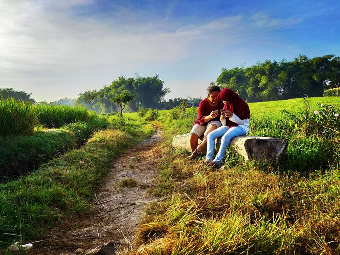 Couple sitting on grass at farm