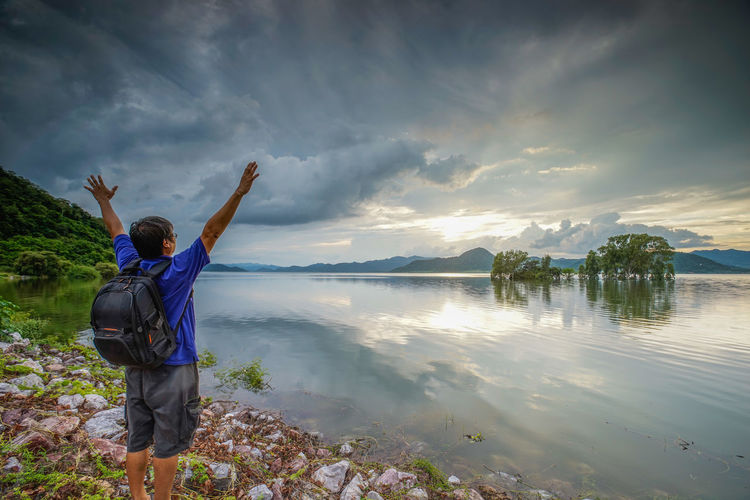 Rear view of man with arms raised standing by lake against sky during sunset