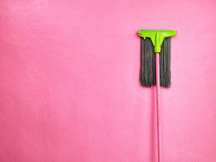 Cleaning product by pink wall
