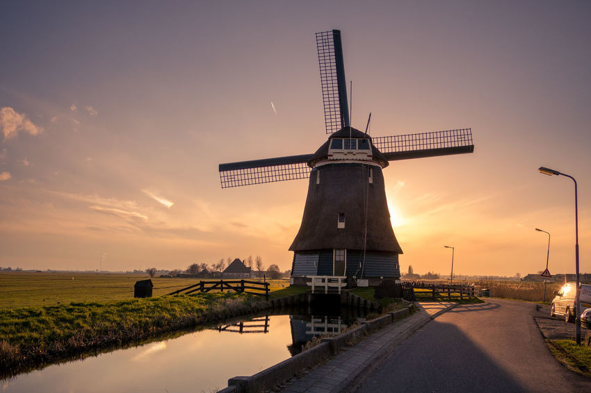 Alternative Energy Beauty In Nature Direction Environment Environmental Conservation Fuel And Power Generation Landscape Nature No People Orange Color Outdoors Renewable Energy Road Rural Scene Sky Sunset Traditional Windmill Transportation Turbine Water Wind Power Wind Turbine