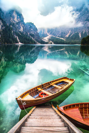Scenic View Of Rowboat In Calm Lake Against Mountains