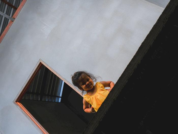 High angle view of boy on orange wall